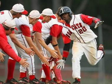 Kentrail Davis is greeted by his Theodore teammates with low fives after hitting a home run against visiting Fairhope in a high school baseball game won by the Bobcats 14-7 on April 3, 2007. (Press-Register file)