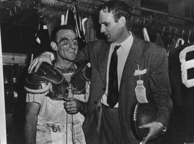 """Kentucky football coach Paul """"Bear"""" Bryant puts an arm around Wilbur Jamerson, co-captain and halfback of the team, in the dressing room after Jamerson sparked the Wildcats to a 13-7 win over Oklahoma in the Sugar Bowl in New Orleans on Jan. 1, 1951. (AP Photo)"""