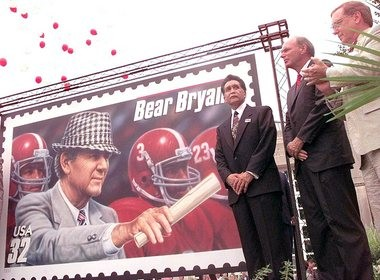 """Officials unveil the Paul """"Bear"""" Bryant postage stamp Aug. 7, 1997 on the University of Alabama campus in Tuscaloosa. From left: U.S. Postal Service Vice-President and Controller Richard Porras, Paul Bryant Jr., and University of Alabama President Andrew Sorenson. (AP Photo/Dave Martin)"""