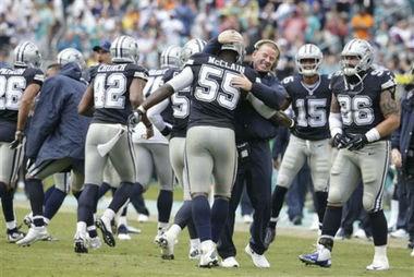 Dallas Cowboys coach Jason Garrett hugs Rolando McClain after the linebacker returned an interception for a touchdown against the Miami Dolphins on Nov. 22, 2015, in Miami Gardens, Fla.