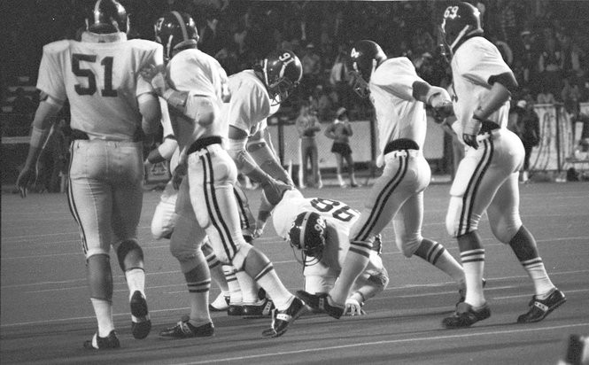Alabama's Leroy Cook (98) crouches on the turf at Legion Field in Birmingham after injuring his right knee during a game against Auburn on Nov. 29, 1975. At left is teammate Bob Baumhower (91). (Photo by Glenn White/Courtesy of the Paul W. Bryant Museum)