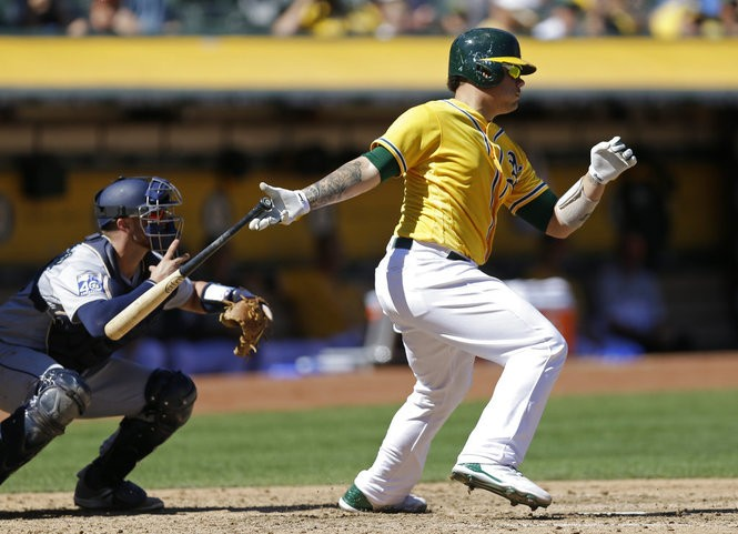 Oakland Athletics catcher Bruce Maxwell hits a run-scoring single during an American League game against the Seattle Mariners on Sept. 27, 2017, in Oakland, Calif.