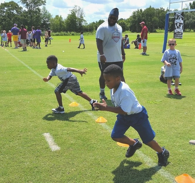 Baltimore Ravens defensive tackle Michael Pierce gets a couple of campers started on the 40-yard dash during the Daphne Pro Camp at Trione Park in Daphne, Ala., on Saturday, July 7, 2018.