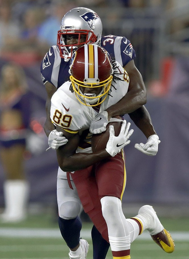 Washington Redskins wide receiver Cam Sims gets tackled by New England Patriots defensive back J.C. Jackson during an NFL preseason game on Thursday, Aug. 9, 2018, in Foxborough, Mass.