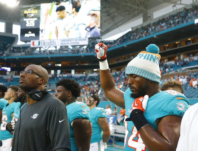 Miami Dolphins defensive end Robert Quinn raises his right fist during the performance of the national anthem before an NFL preseason game against the Tampa Bay Buccaneers on Thursday, Aug. 9, 2018 in Miami Gardens, Fla.