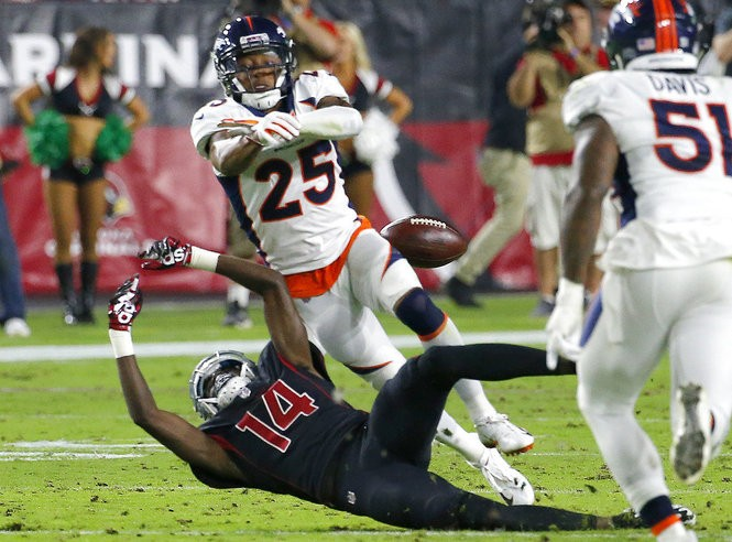 Arizona Cardinals wide receiver J.J. Nelson (14) has a pass knocked away by Denver Broncos cornerback Chris Harris during an NFL game on Thursday, Oct. 18, 2018, in Glendale, Ariz.