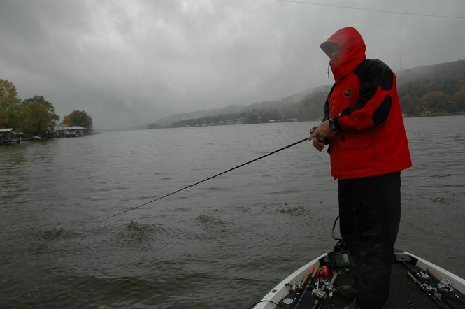 Good rain gear can keep anglers dry even in a downpour, but heavy inflows and muddy water require a change in locations and tactics to find bass.