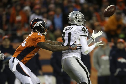 Oakland Raiders safety Brynden Trawick intercepts a pass intended for Denver Broncos wide receiver Cody Latimer during an NFL game on Jan. 1, 2017, in Denver.