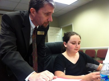 Pelham City Council President Rick Hayes helps out Ellie McPhearson to get ready for the Pelham Youth Government Day council meeting on Monday, April 22, 2013. (Martin J. Reed / mreed@al.com)