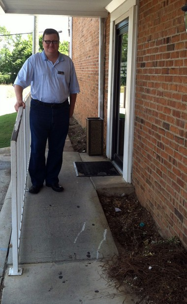 Pelham Public Library Adult Services Coordinator David Smith stands at the doorway leading to the building's rear entrance, which will undergo an improvement project in August to make the entry in line with Americans with Disabilities Act standards. (Martin J. Reed / mreed@al.com)