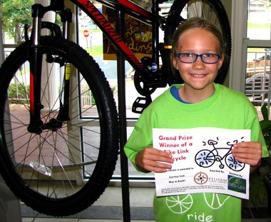 Courtney Cook is the grand prize winner of the Specialized bicycle courtesy of Bike Link at the Pelham Public Libraryas Dig Deep Summer Reading Program carnival on July 23, 2013. (Photo provided)