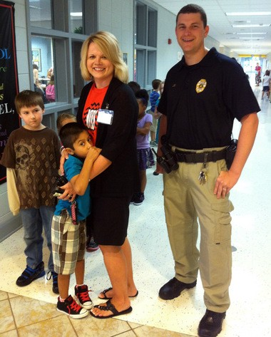 Meadow View Elementary students Matthew Jones and Carlos Guevara-Valle wait next to Principal Rachea Simms and Alabaster School Resource Officer Jamison Lee on Monday, Aug. 19, 2013. (Martin J. Reed)