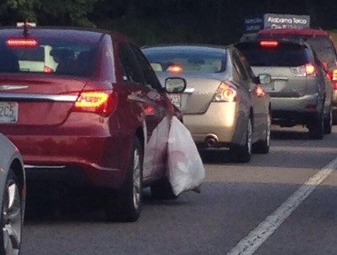 A trash bag caught in a car door dangles along Riverchase Parkway during heavy traffic in October 2013. According to one estimate, debris dropped from vehicles causes 25,000 crashes per year in the U.S.