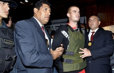 Police officers escort Joran Van der Sloot during a press conference at a police station in Lima, Saturday, June 5, 2010. The young Dutchman wanted in the murder of a 21-year-old Peruvian woman, and who also remains the lone suspect in the 2005 disappearance of U.S. teen Natalee Holloway, arrived in Peru's capital Saturday. (AP)