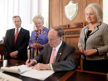 Alabama Gov. Robert Bentley signs into law a bill setting new regulations for abortion clinics on April 9 at the State Capitol in Montgomery, Alabama. From left are House Speaker Mike Hubbard, Lt. Gov. Kay Ivey and Rep. Mary Sue McClurkin. (Julie Bennett/jbennett@al.com)