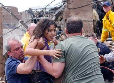 A child is rescued at a school in Moore, Okla., today after a tornado hit the Oklahoma City area. (Associated Press photo by Sue Ogracki)