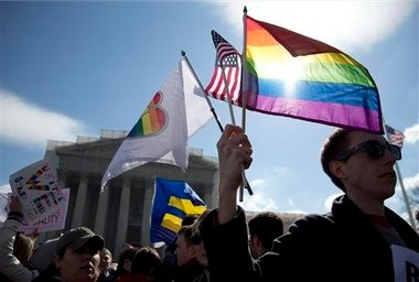 In this March 27, 2013, file photo Kevin Coyne of Washington holds flags in front of the Supreme Court in Washington as the court hears arguments on gay marriage. (AP Photo/Carolyn Kaster, File)