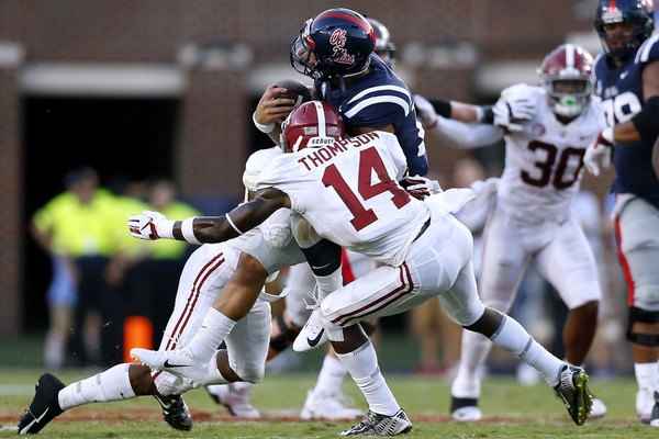 Deionte Thompson (14) of the Alabama Crimson Tide and Xavier McKinney (15) force a fumble on Jordan Ta'amu of the Mississippi Rebels during the first half at Vaught-Hemingway Stadium Saturday night.