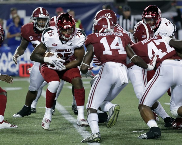 Louisville running back Dae Williams (25) looks for running room against Alabama, including defensive back Deionte Thompson (14), during the second half in Orlando.
