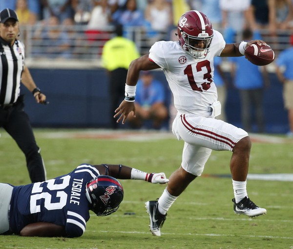 Alabama quarterback Tua Tagovailoa (13) evades a tackle by Mississippi defensive end Tariqious Tisdale (22) during the first half of their NCAA college football game, Saturday, Sept. 15, 2018, in Oxford, Miss. (AP Photo/Rogelio V. Solis) AP