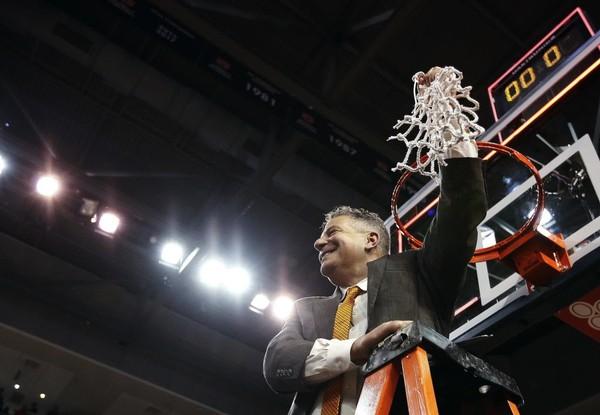 Auburn head coach Bruce Pearl cuts down the net after an NCAA college basketball game against South Carolina, Saturday, March 3, 2018, in Auburn, Ala.