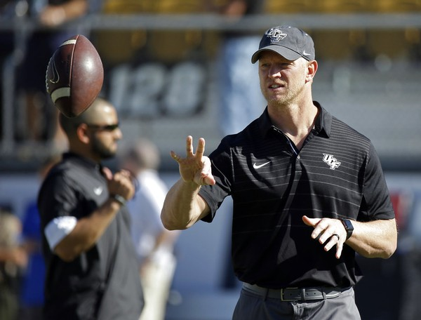 Central Florida head coach Scott Frost tosses a football to one of the players warming up before the American Athletic Conference championship NCAA college football game, Saturday, Dec. 2, 2017, in Orlando, Fla.