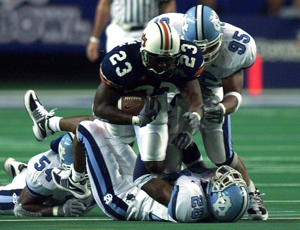 Auburn running back Ronnie Brown (23) is tackled by North Carolina defenders Joey Evans (95), Billy-Dee Greenwood (28) and Marceda Perry (54) in the first quarter in the Peach Bowl at the Georgia Dome on Monday, Dec. 31, 2001, in Atlanta, Ga.