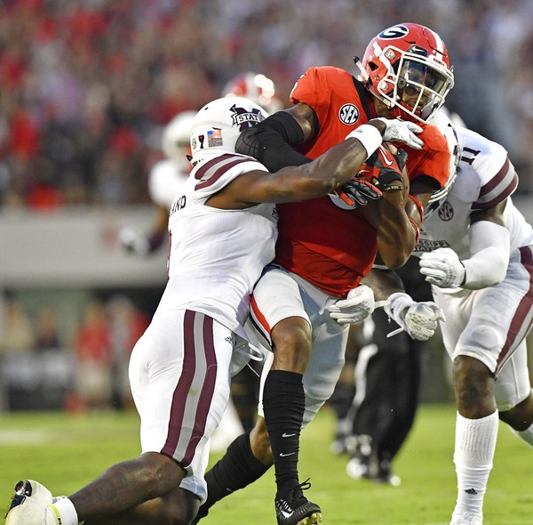 Mississippi State defensive back Tolando Cleveland (7) and linebacker Dezmond Harris (11) stop Georgia wide receiver Terry Godwin (5) during the first of an NCAA college football game, Saturday, Sept. 23, 2017, in Athens, Ga.