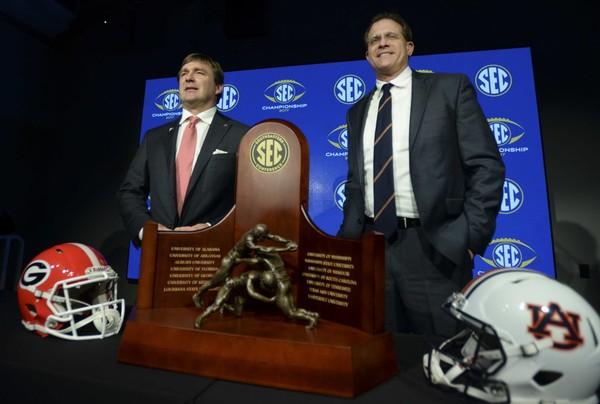 Georgia head coach Kirby Smart and Auburn head coach Gus Malzahn pose with the SEC Championship trophy during a coaches press conference Friday, Dec. 1, 2017, at Mercedes Benz Stadium in Atlanta, Ga.