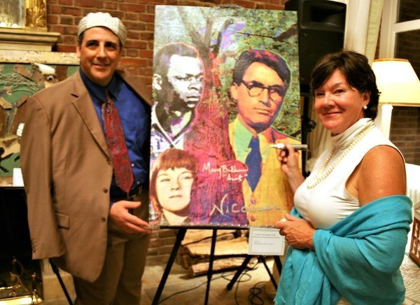 """Mary Badham is shown here signing a """"To Kill a Mockingbird"""" commemorative painting by the artist Nicolosi, left. (Birmingham News file)"""