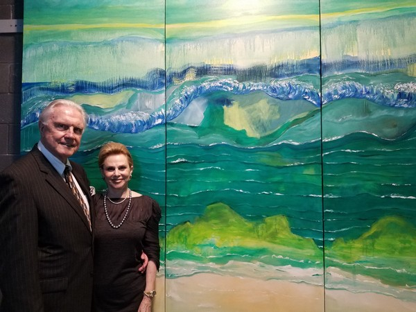 """Susan McCollough and her husband, Dr. E. Gaylon McCollough, stand in front of """"Gulf Ever-Changing,"""" the painting Susan donated to Dauphin Island Sea Lab, at the unveiling on Feb. 16, 2018. (Courtesy DISL)"""