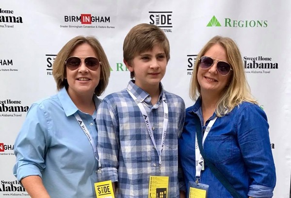 """Cari Searcy, left, and Kim McKeand, right, attend a screening of the documentary """"Alabama Bound"""" with their son, Khaya, at the Sidewalk Film Festival in Birmingham in August. (Facebook photo)"""