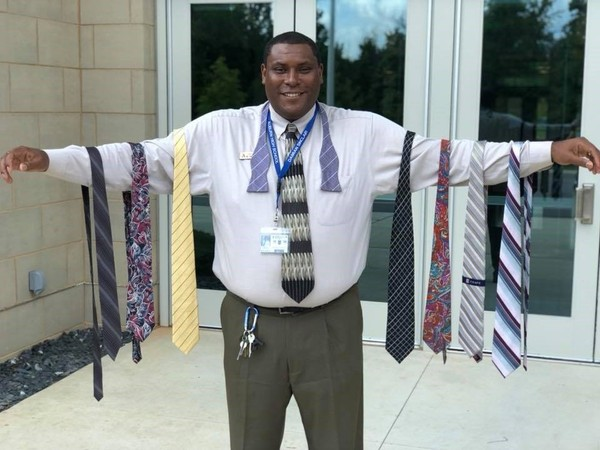 Auburn High School Assistant Principal Damian Sinclair poses with some of the ties that were donated after he initiated Tie-a-Tie Tuesday at the school this week. (Courtesy Auburn High School)