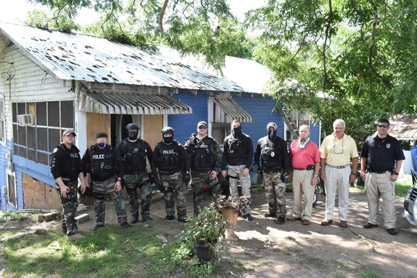 This July 12, 2018 photo shows members of the Jasper, Alabama Police Department with Mayor David O'Mary, second from right and Police Chief J.C. Poe, in front of a house in Frisco, Ala., that was the scene of a drug bust. (Ed Howell/Daily Mountain Eagle via AP)