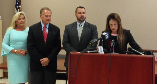 Roy Moore and his wife Kayla, at far left, stand as attorney Melissa Isaak speaks at a press conference in Gadsden Wednesday, July 25, 2018.