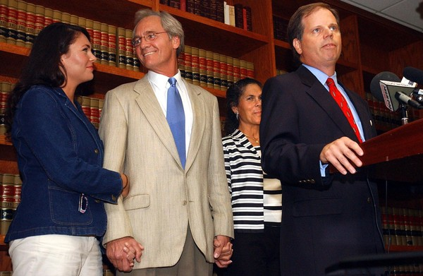 July 5, 2004 Former Gov. Don Siegelman, center, holds hands with his daughter Dana, left, and wife Lori, right, while Attorney Doug Jones, front, addresses the media on July 5, 2004 at the law firm of Whatley Drake. A federal judge kicked-off Jones from Siegelman's case alleging that he saw confidential material while he was a U.S. Attorney.
