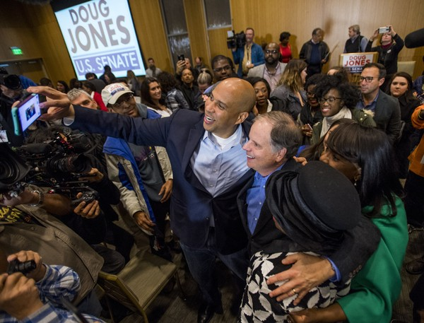 U.S. Sen Cory Booker, D-N.J., and Democratic U.S. Senate candidate Doug Jones take selfies with supporters during a rally at Alabama State University in Montgomery, Ala. on Saturday, Dec. 9, 2017. (Mickey Welsh/The Montgomery Advertiser via AP)/The Montgomery Advertiser via AP)