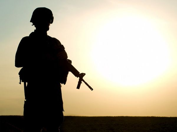 Silhouette of US soldier with rifle against a sunset.