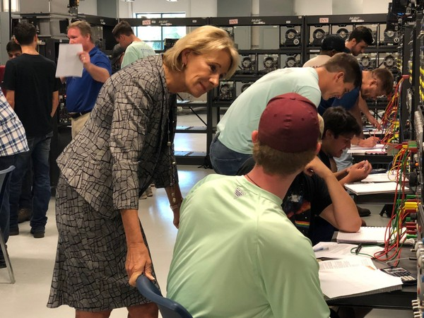 U.S. Education Secretary Betsy DeVos listens as Shelton State Community College students explain what they are learning during her 'Rethink School' visit to Tuscaloosa on Oct. 4, 2018.
