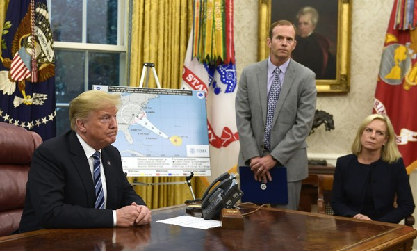 President Donald Trump, left, listens to a reporters question as FEMA Administrator Brock Long, center, and Homeland Security Secretary Kirstjen Nielsen, right, listen during a briefing on Hurricane Florence in the Oval Office of the White House in Washington, Tuesday, Sept. 11, 2018. (AP Photo/Susan Walsh) AP