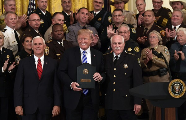 """President Donald Trump, center, poses for a photos with Vice President Mike Pence, front left, and Bristol County, Mass., Sheriff Thomas Hodgson, front right, during an event with sheriffs in the East Room of the White House in Washington, Wednesday, Sept. 5, 2018. Also pictured, behind Pence, are Morgan County Sheriff Ana Franklin and Baldwin County Sheriff Huey """"Hoss"""" Mack. (AP Photo/Susan Walsh)"""
