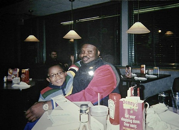 In this undated photo provided by Shelly Covington, Olusegun Olatunji, a Nigerian native, and his son, Micah, pose for a photo at a Denny's restaurant in Bloomington, Ind., in November 2007. Olatunji overstayed a work visa 30 years ago. In 2013, he was convicted of selling counterfeit hats and received a deportation order. Since he was detained by ICE in 2014, he has been appealing to stay in the U.S. for more than three years so that he can support his 15-year-old son's college education. (Shelly Covington via AP)