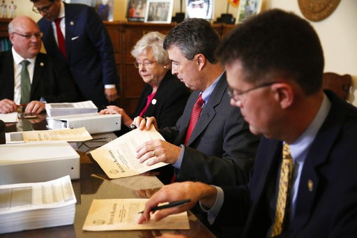 Alabama Secretary of State John Merrill, right, Gov. Kay Ivey, center, and Attorney General Steve Marshall look over documents before they certify the results of the 2017 special election for U.S. Senate, Thursday, Dec. 28, 2017, in Montgomery, Ala. Democrat Doug Jones' historic victory over Republican Roy Moore was declared official Thursday as Alabama election officials certified him the winner of the special Senate election earlier this month, despite claims of voter irregularities from his opponent. (AP Photo/Brynn Anderson)