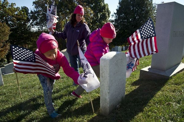 Coast Guard Lt. Cmdr. Melissa Ransom and her daughters participate in the annual Flags Across America event at Arlington National Cemetery in Arlington, Va., Nov. 5, 2016. Coast Guard members, their friends and families placed American and Coast Guard flags on the graves of Coast Guardsmen at the cemetery. The Coast Guard Chief Petty Officers Association's Washington, D.C., chapter holds the annual event the weekend before Veterans Day. Coast Guard photo by Petty Officer 2nd Class Lisa Ferdinando