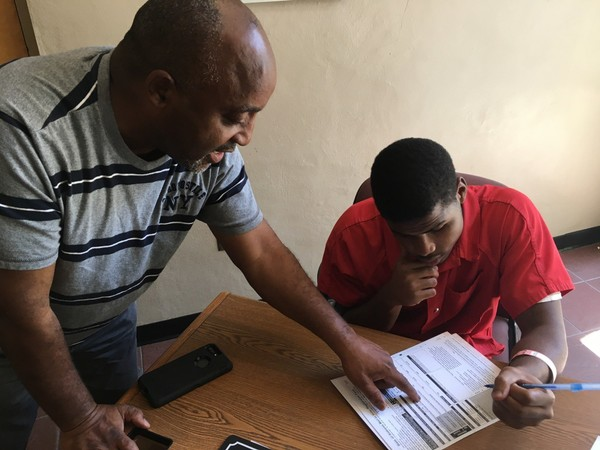 Pastor Kenneth Glasgow helps Dothan City Jail inmate Spencer Trawick fill out a voter registration form inside the jail in June. (Connor Sheets | csheets@al.com)