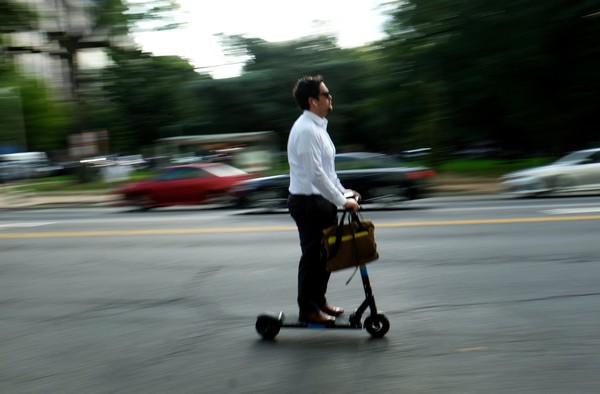 A commuter rides a scooter in Washington, D.C. MUST CREDIT: Washington Post photo by Robert Miller