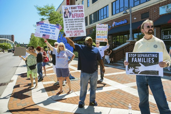 People line up to protest U.S. Attorney General Jeff Sessions and immigration reform at Parkview Field in Fort Wayne, Ind., Thursday, June 14, 2018. (Mike Moore/The Journal-Gazette via AP)