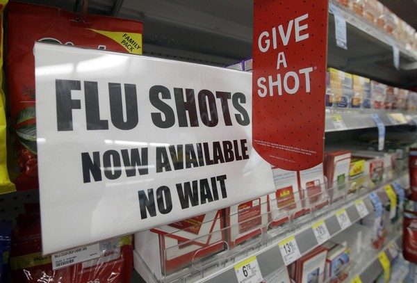 A sign telling customers that they can get a flu shot in a Walgreen store is seen in Indianapolis. (AP Photo/Darron Cummings, File)