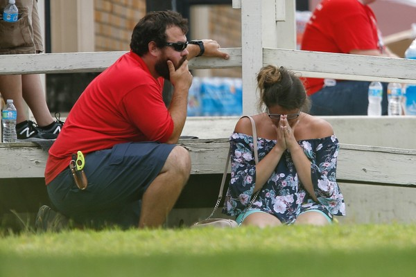 A woman prays in the grass outside the Alamo Gym where parents wait to reunite with their kids following a shooting at Santa Fe High School Friday, May 18, 2018 in Santa Fe. ( Michael Ciaglo / Houston Chronicle )