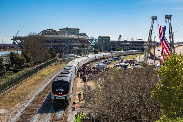 An Amtrak inspection train eases into downtown Mobile in February 2016, receiving a festive reception. Amtrak representatives were traveling the former Gulf Coast line, assessing the prospects of reviving passenger service. It was the last time an Amtrak train traveled along the CSX line along the Gulf Coast. A Wednesday deadline looms for Alabama Gov. Kay Ivey to make a financial commitment on whether to match federal sources for the restart of Amtrak along the Gulf Coast. (photo by Marc Glucksman / Amtrak)